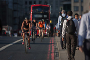 Cyclists in front of a bus, cross with commuters over London Bridge, from the City of London to the south bank of the Thames on 8th September 2016, in Southwark, England UK. Pedalling over the bridge is a woman followed by others and the bus in late summer sunshine.