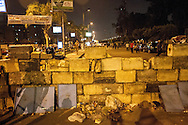 Morsi supporters erect barricades, walls and checkpoints around their sit-in in Nassr city. Violent clashes have broken out in recent days, leaving at least 30 people dead.