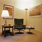 """A black leather """"Stressless"""" chair and footrest on its left, in the middle of a plain room with a Monet Waterlilies poster on the right wall and a Paul Klee poster behind it, a wooden table with a brass plated lamp on the left and a standing lamp in the rear corner. The carpet is a very plain, beige color wall to wall."""