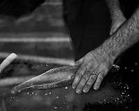 Cook cleaning a fish. Afternoon Street Photography in Cascias. Image taken with a Fuji X-T3 camera and 35 mm f/1.4 lens.
