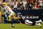 Oct 14, 2012; Houston, TX, USA; Green Bay Packers quarterback Aaron Rodgers (12) breaks a tackle attempt by Houston Texans outside linebacker Connor Barwin (98) during the first quarter at Reliant Stadium. Mandatory Credit: Thomas Campbell-thomasgcampbell.com