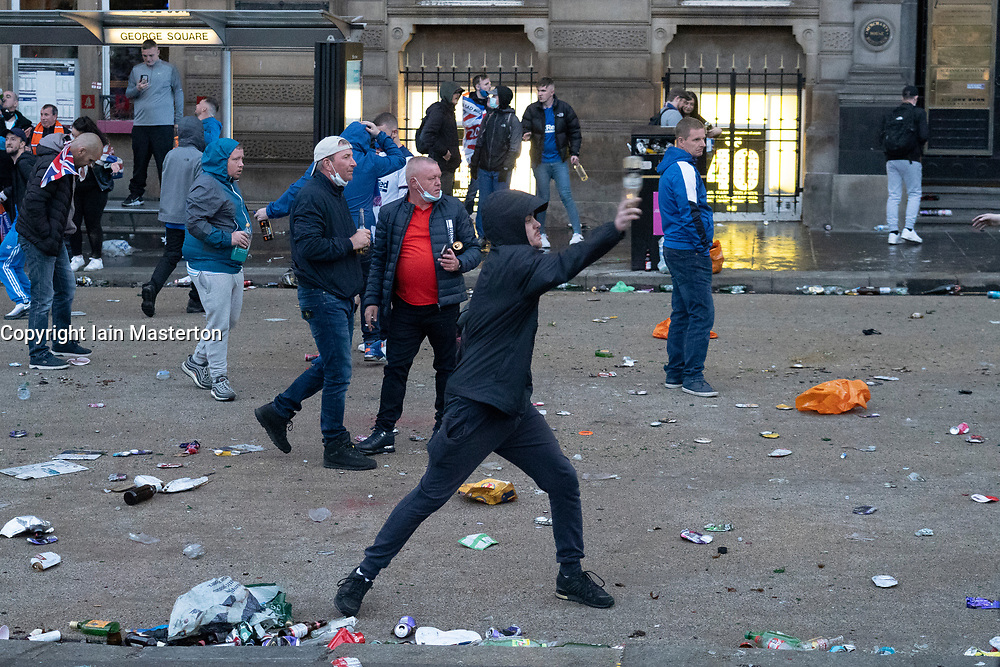 Glasgow, Scotland, UK. 15 May 202. Rangers football supporters  celebrating 55th league victory are cleared from George Square by police in riot gear on Saturday evening. In very violent scenes police were pelted with bottles and items from a nearby construction site as police pushed the supporters into the south west corner of the square. Pic Man throws bottle towards police lines. Iain Masterton/Alamy Live News.