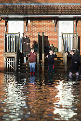 © London News Pictures. 12/02/2014. Egham, UK.  Two young boys give a defiant thumbs up outside their property which is surrounded by flood water in Egham, Surrey. Torrential rain in the area is due to raise water levels increasing the risk of further flooding. Photo credit : Ben Cawthra/LNP