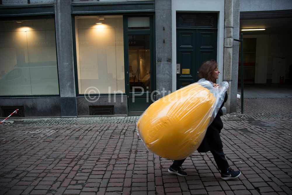 Woman carrying a large yellow bean bag on the street in Brussels, Belgium. The Brussels-Capital Region is a region of Belgium comprising 19 municipalities, including the City of Brussels.