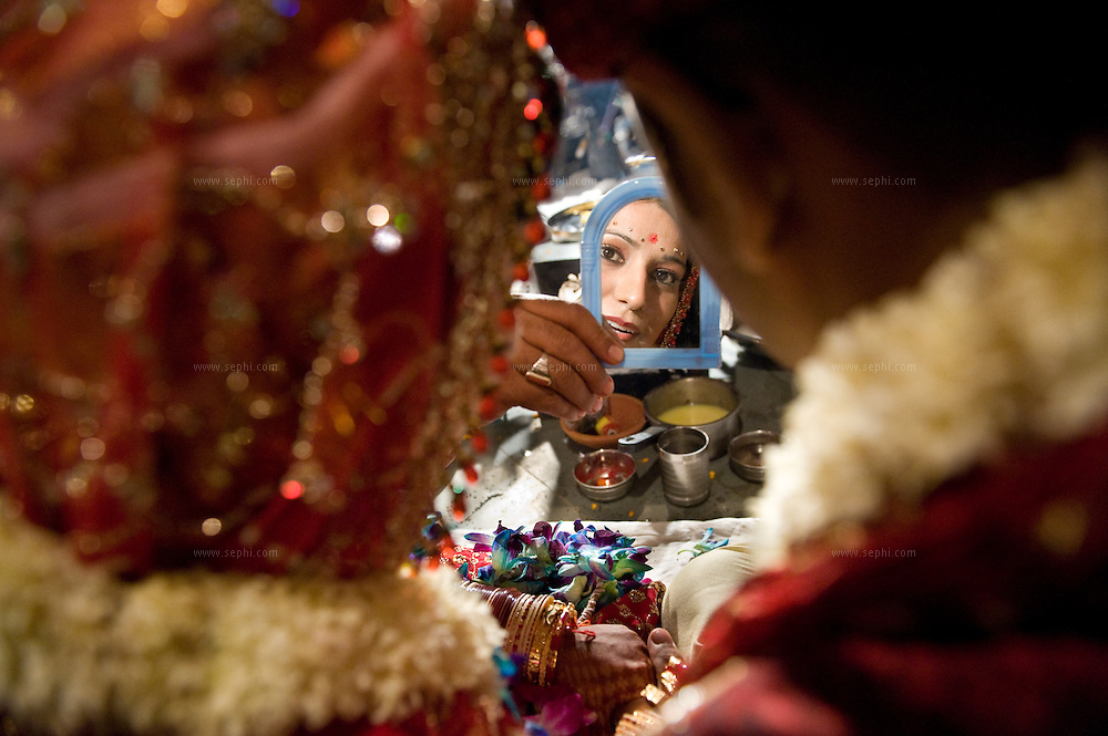 At a Kashmiri Pandit wedding in New Delhi, the priest holds a small mirror in front of the couple to enable the bride and groom to see each others reflection. This practice originally evolved  to help the new couple overcome their nervousness, having been introduced for the first time just before the wedding. November 2008