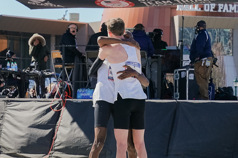 Galen Rupp (facing away from camera) embraces Abdi Abdirahman after the 2020 U.S. Olympic marathon trials in Atlanta on Saturday, Feb. 20, 2020. Rupp finished first and Abdirahman came in third, placing him in his fifth Olympics. Photo by Kevin D. Liles for The New York Times