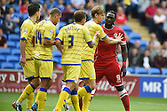 Kenwyne Jones  of Cardiff city ® is pushed away by Sheff Wed capt Glen Loovens. Skybet football league championship match, Cardiff city v Sheffield Wed at the Cardiff city stadium in Cardiff, South Wales on Saturday 27th Sept 2014<br /> pic by Andrew Orchard, Andrew Orchard sports photography.