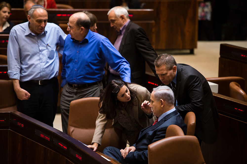Israeli Prime Minister Benjamin Netanyahu (sitting R) speaks with ministers and parliament members at the Knesset, Israel's parliament in Jerusalem, on December 3, 2014, during the vote to dissolve the parliament. Israeli legislators voted Wednesday to dissolve the parliament, and they set March 17 as the date for parliamentary elections, two years ahead of schedule, following a crisis within Prime Minister Netanyahu's coalition government.