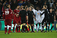 Tempers flare at the end of the match as referee Neil Swarbrick © calms everyone down. Premier league match, Swansea city v Liverpool at the Liberty Stadium in Swansea, South Wales on Monday 22nd January 2018. <br /> pic by  Andrew Orchard, Andrew Orchard sports photography.