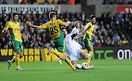 Swansea's Michu has a shot at goal despite the attentions of Aleksei Kozlov.<br /> UEFA Europa league match, Swansea city v FC Kuban Krasnodar at the Liberty Stadium in Swansea, South Wales on Thursday 24th October 2013. pic by Phil Rees, Andrew Orchard sports photography,