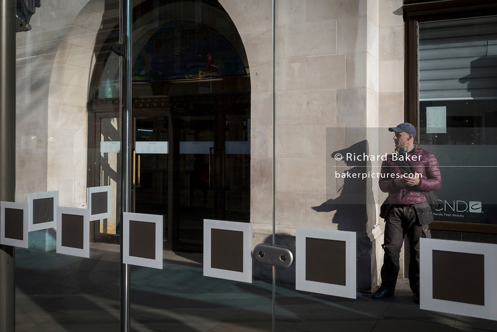 A Londoner and squares on the glass screens at a bus stop in Kingston, on 7th November 2019, in London, England