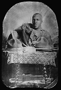 World War I  1914-1918:  African-American soldier seated behind table, pencil in hand and facing front, with two hats on table.
