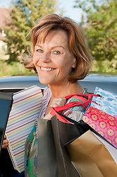 Senior woman getting into car with shopping bags