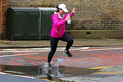 © Licensed to London News Pictures. 07/08/2021. London, UK. A woman jumps over a puddle of water in north London caused by heavy rain. According to the Met Office, thunderstorms and heavy rain is expected in some parts of England this weekend. Photo credit: Dinendra Haria/LNP