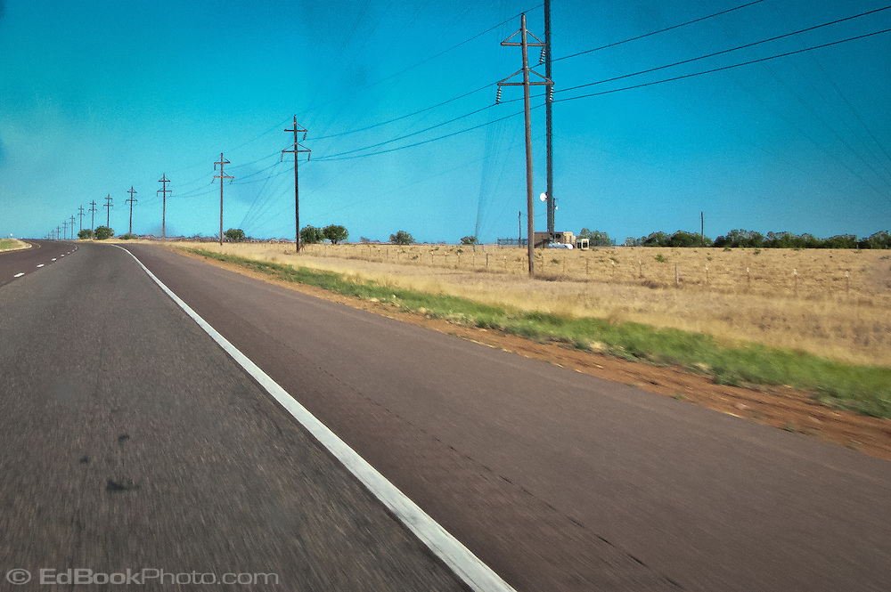 a power line and interstate 20 pass by a radio transmitter site tower in flat west Texas, USA