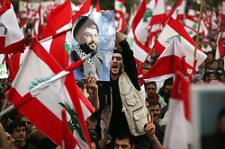 A man holds a poster of Hezbollah chief Sheikh Hassan Nasrallah, Beirut, Lebanon, March 8, 2005. Hundreds of thousands of pro-Syrian protesters gather and chant anti-American slogans. Hezbollah, the militant Shiite Muslim group, called for a nationwide demonstration against foreign intervention and to counter weeks of massive anti-Syrian rallies.