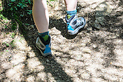 Female hiker hikes in the forest. Close up of the feet and shoes Model release available
