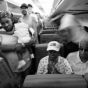 NEW ORLEANS, LA - September 4, 2005:  Evacuees from New Orleans were being flown to the city's airport via helicopter and unloaded on the tarmac. Unloaded on the tarmac in a scene similar to that of a war zone evacuation, they were then hustled from the helicopter onto waiting cargo carts ( normally used to move luggage) and rushed amid a throng of volunteers and into the airport where they received medical attention. Shortly after entering the airport, evacuees were screened and divided nto groups of 50 and told to go to a certain boarding gate. Evacuees only find out the destination of the flight, and their new temporary home, after boarding the flight. (Photo by Todd Bigelow/Aurora)..Chaney family is flown to West Palm, Beach, Florida. They had no idea where they were heading until the plane's doors were closed.......Members of the Chaney family, Kenneth (large man with straw hat), Anthony (other man with shorts), Elaine (younger woman), and Julia (woman with MLK prayer fan and hat--she's Ken's and Anthony's mother). Joseph (yellow shirt,using cane to walk) and Velma (red shorts and white ball cap). Joseph and Velma are Elaine's parents...... (Last name TK--check with reporter ken lee)..
