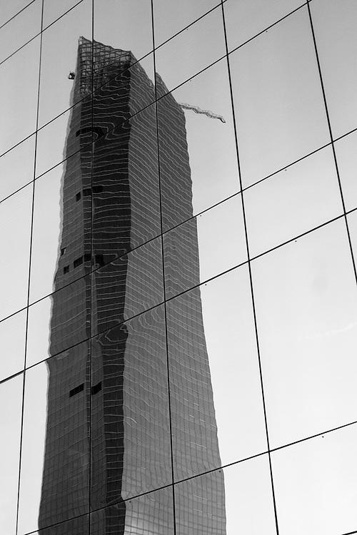 La Torre de Cristal, una de las cuatro Torres Madrid Arena, de reciente construción en el Paseo de la Castellana de Madrid, reflejada sobre la fcahada del edificio sede de Repsol