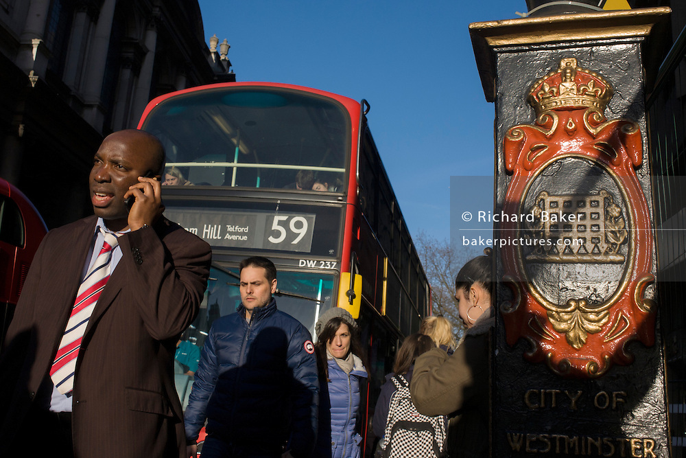 Late afternoon pedestrians walk into bright sunlight on the Strand in central London.