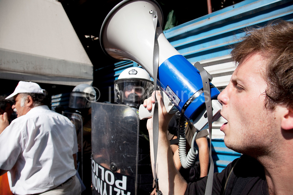Riot police presence as a student shouts into a loud hailer to demonstrate against austerity measures and planned education reforms in Athens. The demonstration is against an education reform bill which aims to improve the operation of universities.