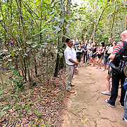 A tour guide explains to tourist what the American bombing campaign did to the surrounding landscape. At left of the frame is one of the many bomb craters that pockmark the area. The Cu Chi tunnels, northwest of Ho Chi Minh City, were part of a much larger underground tunnel network used by the Viet Cong in the Vietnam War. Part of the original tunnel system has been preserved as a tourist attraction where visitors can go down into the narrow tunnels and see exhibits on the defense precautions and daily life of the Vietnamese who lived and fought there.