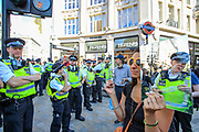 A demonstrator holds up a mirror towards the Police officers during the group's 'Impossible Rebellion' series of actions at Oxford Circus in central London, on Wednesday, August 25, 2021. - Climate change demonstrators from environmental activist group Extinction Rebellion continued with their latest round of protests in central London, promising two weeks of disruption. (VX Photo/ Vudi Xhymshiti)