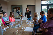 A female tour guide talks as she pours English Balfour Brute sparkling wine for tasting to a group of visitors at Hush Heath Winery, Staplehurst, Kent, England, UK.  (photo by Andrew Aitchison / In pictures via Getty Images)