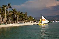 Yellow and white sailing boat near white sand beach on boracay island, Philippines.