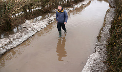 © Licensed to London News Pictures. 05/03/2018. Bodden, UK. Tim Walters walks through flood water left by melted snow, on a previously blocked road at Bodden near Shepton Mallet, Somerset after a week of heavy snow. . Photo credit: Jason Bryant/LNP