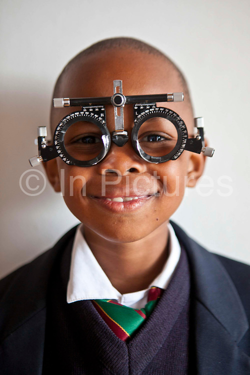 A young African school boy wears an eye test frame and smiles happily in a classroom in Zonnebloem School, Cape Town, South Africa.  The eye test is being provided by Mullers Opticians who volunteer their staff to visit schools and perform eye tests on all children in school grade 2.