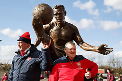 © licensed to London News Pictures. London, UK 22/02/2014. Arsenal fans having their pictures taken with a newly unveiled Dennis Bergkamp statue ahead of Arsenal's premier league fixture against Sunderland at Emirates Stadium in London. Photo credit: Tolga Akmen/LNP