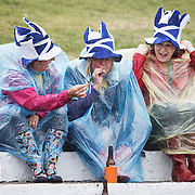 Competitors prepare for the Highland Dancing at the Cowal Highland Gathering 2014 at Dunoon Stadium, Dunoon, Scotland. 3 women in the small crowd struggle against the wind and rain.  Picture Robert Perry 29/ 08/ 2014