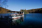 Boat on lake, near small jetty, tourists on boat. Plitvice National Park, Croatia