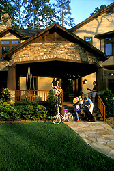 Stock photo of the exterior of a house with the family on the front porch