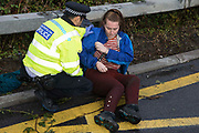 A Metropolitan Police officer arrests an Insulate Britain climate activist who had previously blocked a M25 slip road at Junction 14 close to Heathrow airport as part of a campaign intended to push the UK government to make significant legislative change to start lowering emissions on 27th September 2021 in Colnbrook, United Kingdom. The activists are demanding that the government immediately promises both to fully fund and ensure the insulation of all social housing in Britain by 2025 and to produce within four months a legally binding national plan to fully fund and ensure the full low-energy and low-carbon whole-house retrofit, with no externalised costs, of all homes in Britain by 2030.