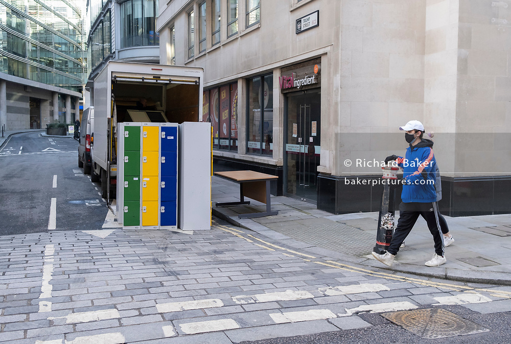 A pedestrian walks past a contractor's van which is being loaded with office locker furniture from a nearby building during the third lockdown of the Coronavirus pandemic, in the City of London, the capital's financial district, on 10th February 2021, in London, England.