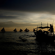 Sunset at White Beach as a local tourists boat pushes away from the beach on October 3, 2008 in Boracay Island, the Philippines. Photo Tim Clayton..Asian tourists at White Beach, Boracay Island, the Philippines...The 4 km stretch of White beach on Boracay Island, the Philippines has been honoured as the best leisure destination in Asia beating popular destinations such as Bali in Indonesia and Sanya in China in a recent survey conducted by an International Travel Magazine with 2.2 million viewers taking part in the online poll...Last year, close to 600,000 visitors visited Boracay with South Korea providing 128,909 visitors followed by Japan, 35,294, USA, 13,362 and China 12,720...A popular destination for South Korean divers and honeymooners, Boracay is now attracting crowds of tourists from mainland China who are arriving in ever increasing numbers. In Asia, China has already overtaken Japan to become the largest source of outland travelers...Boracay's main attraction is 4 km of pristine powder fine white sand and the crystal clear azure water making it a popular destination for Scuba diving with nearly 20 dive centers along White beach. The stretch of shady palm trees separate the beach from the line of hotels, restaurants, bars and cafes. It's pulsating nightlife with the friendly locals make it increasingly popular with the asian tourists...The Boracay sailing boats provide endless tourist entertainment, particularly during the amazing sunsets when the silhouetted sails provide picture postcard scenes along the shoreline...Boracay Island is situated an hours flight from Manila and it's close proximity to South Korea, China, Taiwan and Japan means it is a growing destination for Asian tourists... By 2010, the island of Boracay expects to have 1,000,000 visitors.