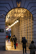 Commuters walk beneath the ironwork of the Ritz Hotel and the covered arcade that leads towards Green Park underground station on Piccadilly, on 3rd February 2021, in London, England.
