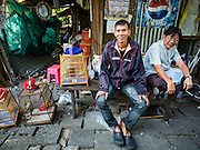 """08 FEBRUARY 2017 - BANGKOK, THAILAND: Men chat while their birds get fresh air in Pom Mahakan. The residents of the old fort are known for their community of song bird enthusiasts. More than 40 families still live in Pom Mahakan, a slum community in a 19th century fort in Bangkok. City officials are trying to move them out of the fort but members of the community refuse to leave. NGOs and historic preservation organizations are working with the community to help them find a way to stay. After several deadlines passed, residents were told that they have to leave by the end of February. They submitted another proposal to the city this week to turn their community into a """"living heritage museum"""" and hope to get the eviction deadline extended until late March.       PHOTO BY JACK KURTZ"""