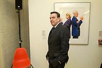 """14 FEB 2005, BERLIN/GERMANY:<br /> Gerhard Schroeder, SPD, Bundeskanzler, laeuft - die Haende in den Hosentaschen - an einem Bild mit Angela Merkel und Edmund Stoiber vorbei, in der Ausstellung """"Die Kunst des Spiegel"""", C/O Berlin, The Cultural Forum for Photography<br /> IMAGE:20050214-02-006<br /> KEYWORDS: Titelbilder, Gerhard Schröder"""