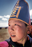 A young contestant at a Nadaam horserace (about 20 Km speed race) wearing the traditional race hat. Youngest racer are between 5 and 7 years old.<br /> Winning a race is quite the feat—prizes for winners include horses, and sometimes cars.<br /> Near Moron town, Khövsgöl province.