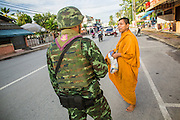 25 OCTOBER 2012 - PATTANI, PATTANI, THAILAND:  A Buddhist monk talks to his soldier escort bodyguard during his morning alms rounds in Pattani, Thailand. More than 5,000 people have been killed and over 9,000 hurt in more than 11,000 incidents, or about 3.5 a day, in Thailand's three southernmost provinces and four districts of Songkhla since the insurgent violence erupted in January 2004, according to Deep South Watch, an independent research organization that monitors violence in Thailand's deep south region that borders Malaysia.    PHOTO BY JACK KURTZ
