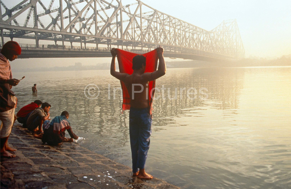 A dawn bather covers his face with red cloth as sun rises over Hooghler River, KolIkata. It is dawn in Calcutta, West Bengal, India and on the West bank of the Hooghly River the sun is rising from across the Howrah Bridge. Six bathers are either drying themselves after washing in the river, or are undressing to do so. It is a scene of inner-peace, a tranquillity surrounded by the chaotic pace of Indian life in this city. The engineering of the bridge stretches across the water towards the city beyond. The bridge is one of three on the Hooghly River and is a famous symbol of Kolkata and West Bengal. Bearing the daily weight of approximately 150,000 vehicles and 4,000,000 pedestrians. It is one of the longest bridges of its type in the world. The Hooghly River is an approximately 260 km long distributary of the Ganges River.