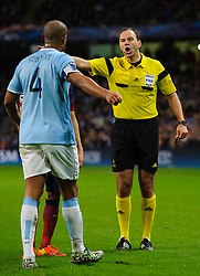 referee Jonas Eriksson (SWE) shouts at Man City Defender Vincent Kompany (BEL) after he fouls Barcelona Defender Gerard Pique (ESP)  - Photo mandatory by-line: Rogan Thomson/JMP - Tel: 07966 386802 - 18/02/2014 - SPORT - FOOTBALL - Etihad Stadium, Manchester - Manchester City v Barcelona - UEFA Champions League, Round of 16, First leg.