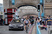 After the lifting of both bascules that allowed a tall boat boat to pass underneath, cyclists and traffic cross during the evening rush-hour, on 11th June 2021, in London, England.