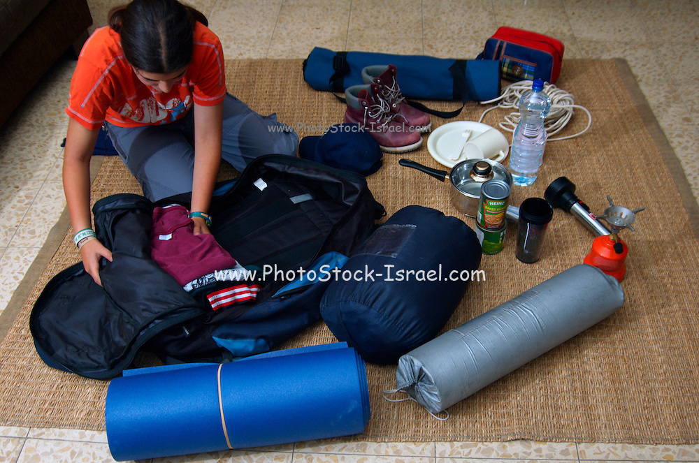 A young girl of 12 packing her backpack for a camping trip