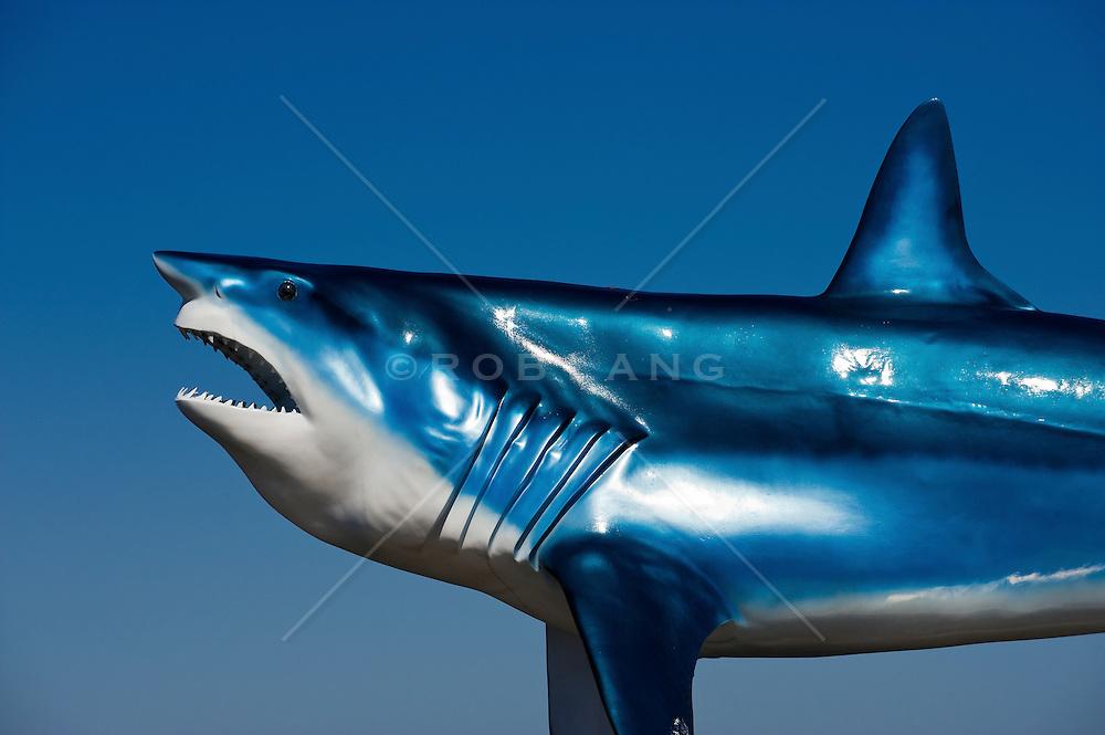 Great white shark sculpture against a clear blur sky