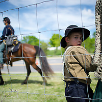 A boy stands with his mother as Union cavalry pass by during the Chancellorsville 150th reenactment in Spotsylvania, VA on May 4, 2012.