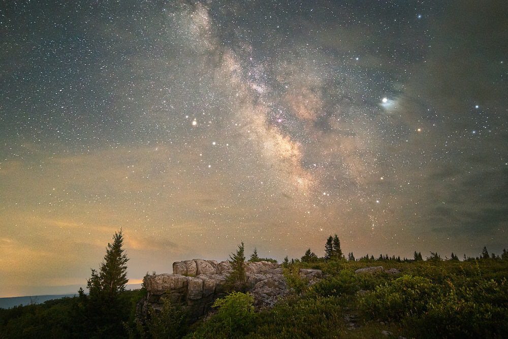 Late evening twilight outlines familiar shapes of rocky outcrops and flagged pine as the Milky Way stands in view across the high plains of Dolly Sods in West Virginia.